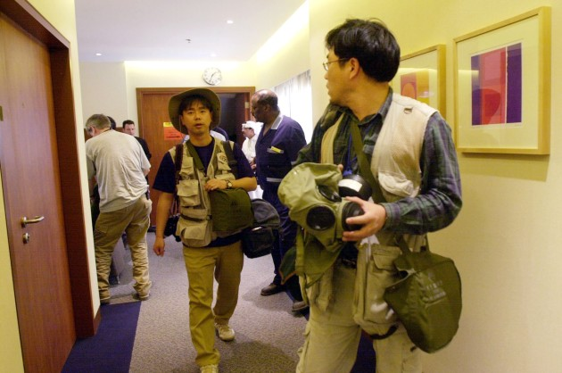 Foreign journalists and hotel guests put on their gas masks as civil alert sirens ring throughout the city in a hotel in Kuwait City, Thursday, March 20, 2003.  Before noon, the Kuwait Ministry of Defense said that four missiles were launched into Kuwait from Iraq.  No injuries or damage were reported. (AP Photo/Wally Santana)